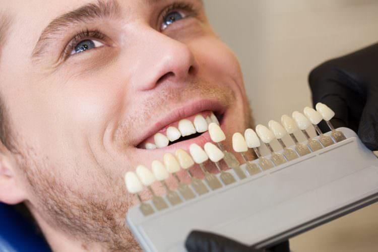 man in dental chair looking at his improved whitened teeth with whiten teeth guide