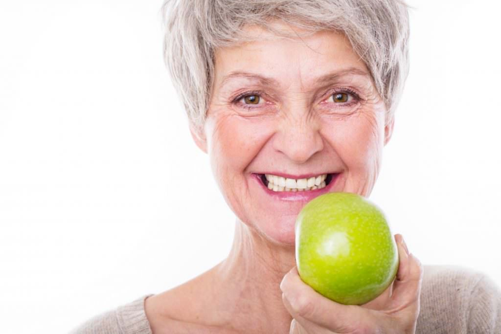 Older lady holding an apple with her new shiny white teeth in her advanced dentures iDentures