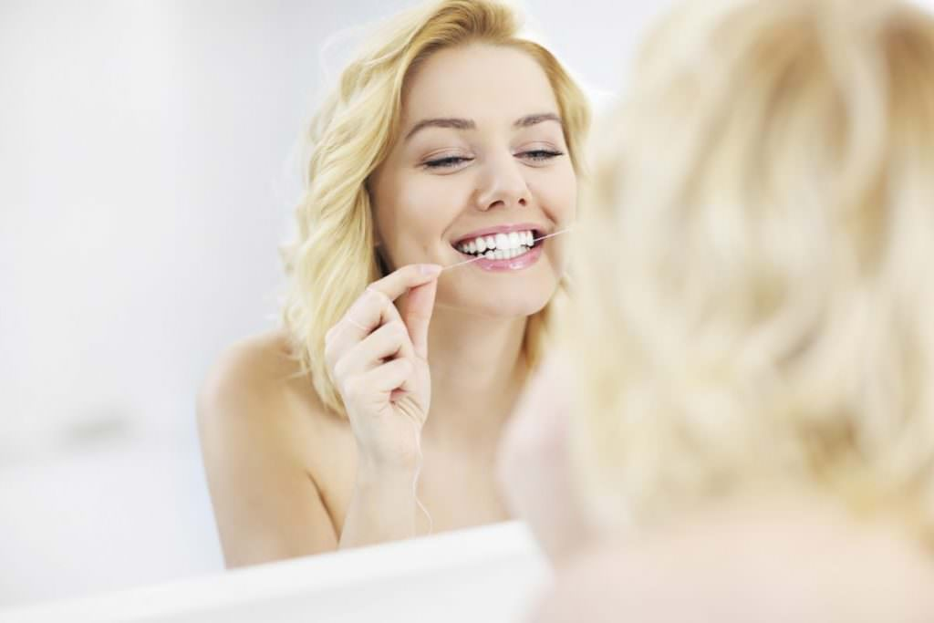 A picture of a young happy woman using dental floss in the bathroom Spedding dental clinic carlisle