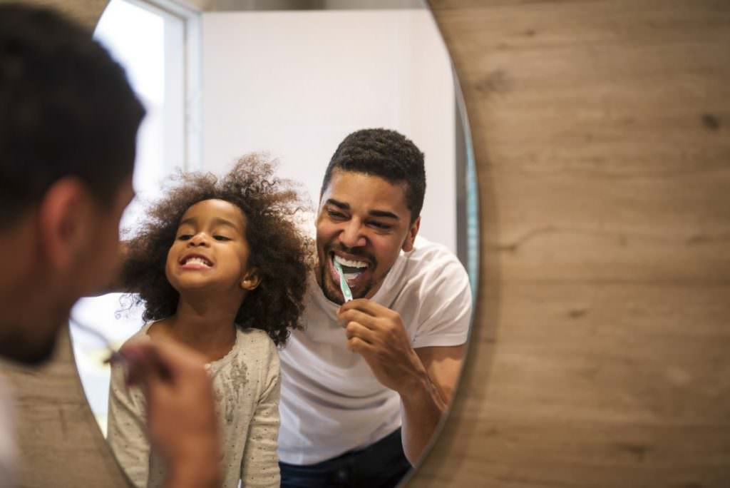 Father and daughter cleaning teeth as part of good family dentistry